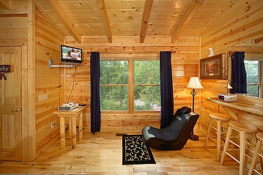 video game corner in lofted game room with chairs and game consoles at brownie bear a 1 bedroom cabin rental located in gatlinburg