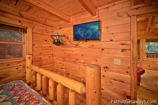 Flat screen tv mounted to wall at foot of bed in a bedroom at Black Bear Magic, a 4-bedroom cabin rental located in Gatlinburg