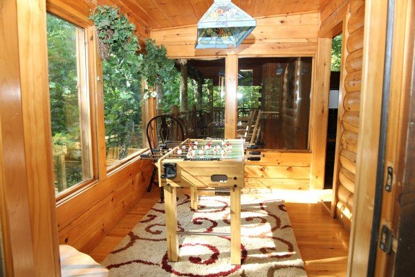 Foosball table with covered porch in the background at Black Bear Magic, a 4-bedroom cabin rental located in Gatlinburg