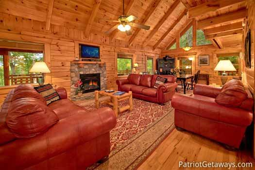 Living room with stone fireplace and sofas at Black Bear Magic, a 4-bedroom cabin rental located in Gatlinburg