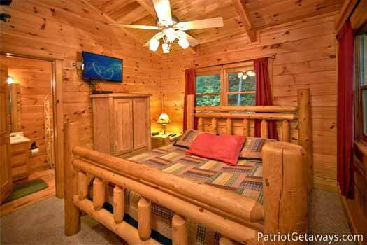 Second floor king sized bed in bedroom with ensuite at Black Bear Magic, a 4-bedroom cabin rental located in Gatlinburg