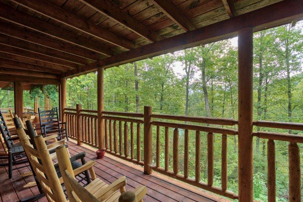 Rocking chairs on a covered deck looking into the woods at Black Bear Magic, a 4-bedroom cabin rental located in Gatlinburg
