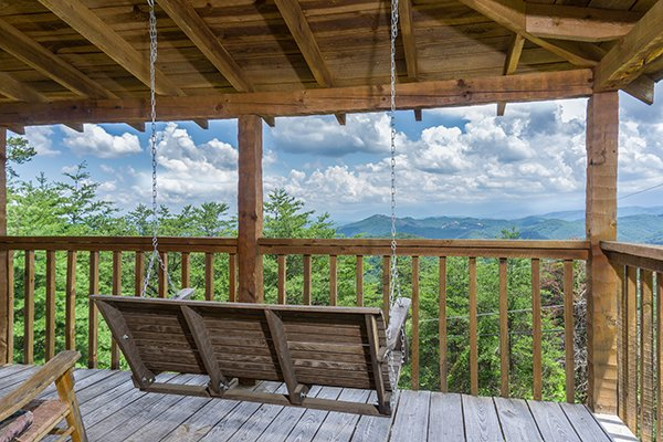 Porch swing on a covered deck overlooking the mountains at Mountain Glory, a 1 bedroom cabin rental located in Pigeon Forge