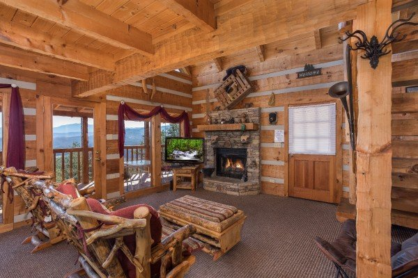Living room with log furniture, a fireplace, TV, and deck access at Mountain Glory, a 1 bedroom cabin rental located in Pigeon Forge