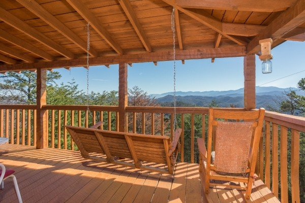 Porch swing and rocking chair on a covered deck at Mountain Glory, a 1 bedroom cabin rental located in Pigeon Forge
