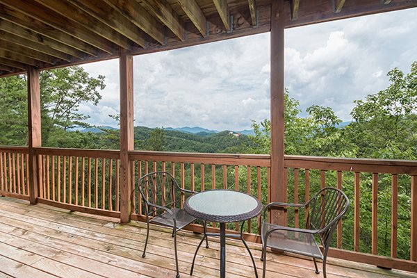 Bistro set on the covered deck at 1 Amazing View, a 2 bedroom cabin rental located in Pigeon Forge