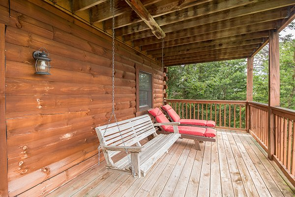 porch swing and two chaise loungers at 1 amazing view a 2 bedroom cabin rental located in pigeon forge