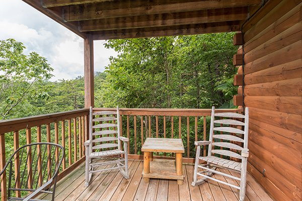 Rocking chairs and a table on the deck at 1 Amazing View, a 2 bedroom cabin rental located in Pigeon Forge