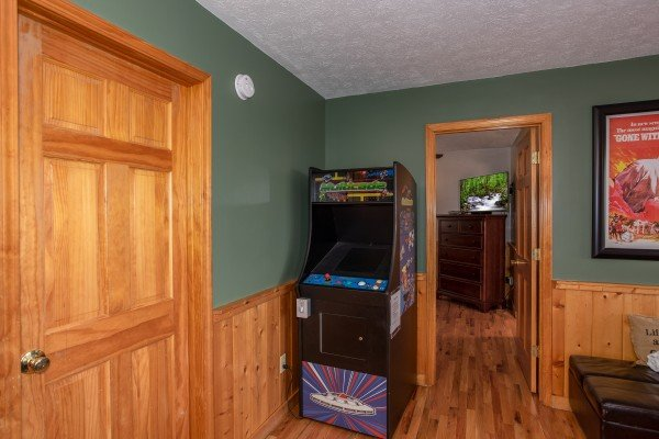 Arcade game in the game room at Burrow Inn, a 4-bedroom cabin rental located in Pigeon Forge