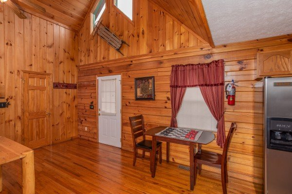 Table with seating for two and a checker game at Burrow Inn, a 4-bedroom cabin rental located in Pigeon Forge
