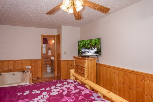 Bedroom with a large log bed, in-room jacuzzi, dresser, and television at Burrow Inn, a 4-bedroom cabin rental located in Pigeon Forge