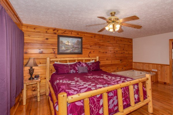 Log bed next to an end table with a lamp and a jacuzzi at Burrow Inn, a 4-bedroom cabin rental located in Pigeon Forge