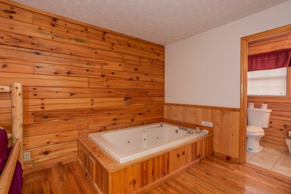Jacuzzi in the first bedroom next to an en suite at Burrow Inn, a 4-bedroom cabin rental located in Pigeon Forge