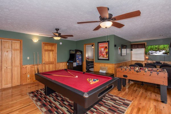 Red felted pool table with an arcade game and foosball table at Burrow Inn, a 4-bedroom cabin rental located in Pigeon Forge