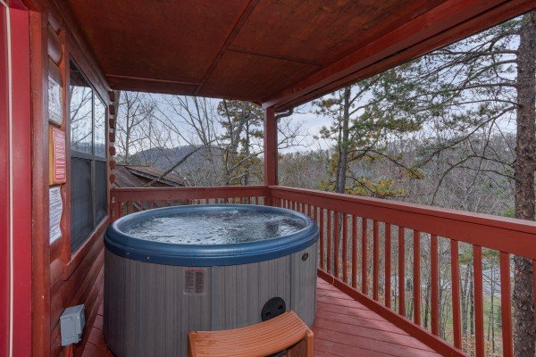 Hot tub on a covered deck at Burrow Inn, a 4-bedroom cabin rental located in Pigeon Forge