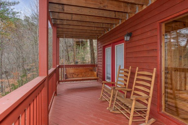 Porch swing and two rocking chairs on a covered deck at Burrow Inn, a 4-bedroom cabin rental located in Pigeon Forge