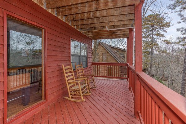 Two rocking chairs on a covered deck at Burrow Inn, a 4-bedroom cabin rental located in Pigeon Forge