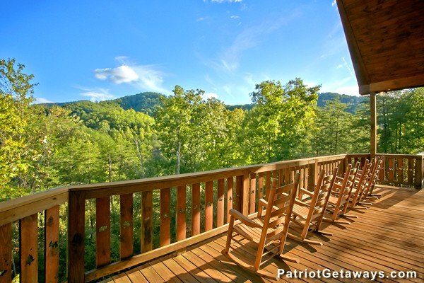 Rocking chairs on a deck looking at wooded mountain views at Pot O' Gold, a 4 bedroom cabin rental located in Pigeon Forge