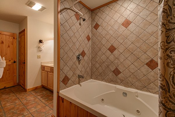 Bathroom with a jacuzzi and shower at Pot O' Gold, a 4 bedroom cabin rental located in Pigeon Forge