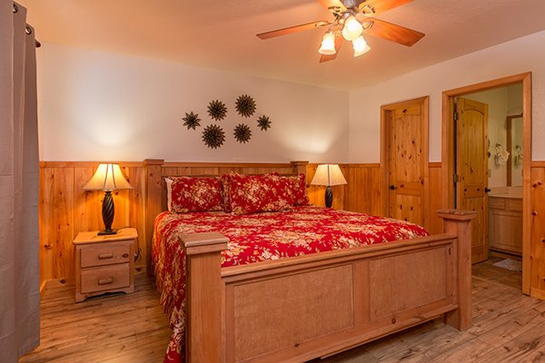 King sized bed in the downstairs bedroom at Pot O' Gold, a 4 bedroom cabin rental located in Pigeon Forge
