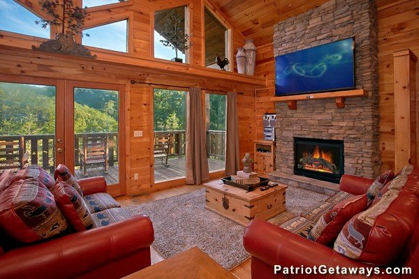 Living room with large windows, fireplace, and TV at Pot O' Gold, a 4 bedroom cabin rental located in Pigeon Forge