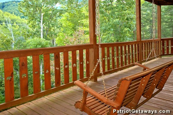 Swing on a covered porch at Pot O' Gold, a 4 bedroom cabin rental located in Pigeon Forge