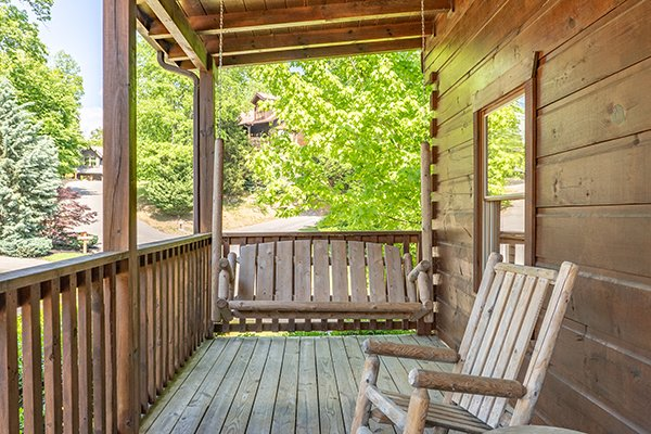 Porch swing on a covered deck at Livin' Simple, a 2 bedroom cabin rental located in Pigeon Forge