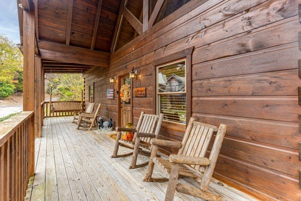 Covered deck with Adirondack chairs at Livin' Simple, a 2 bedroom cabin rental located in Pigeon Forge