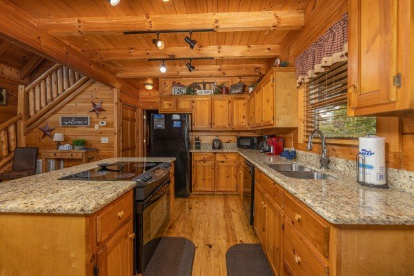 Galley kitchen with black appliances and granite counters at Livin' Simple, a 2 bedroom cabin rental located in Pigeon Forge