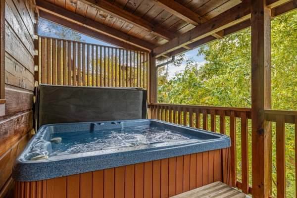 Hot tub with privacy fence on a covered deck at Livin' Simple, a 2 bedroom cabin rental located in Pigeon Forge