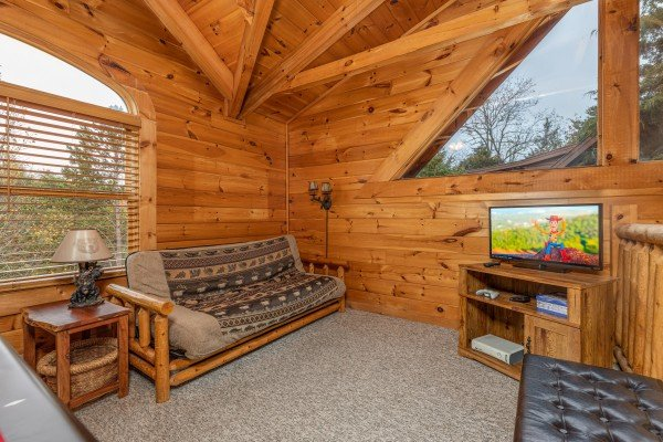 Futon and TV in the loft at Livin' Simple, a 2 bedroom cabin rental located in Pigeon Forge