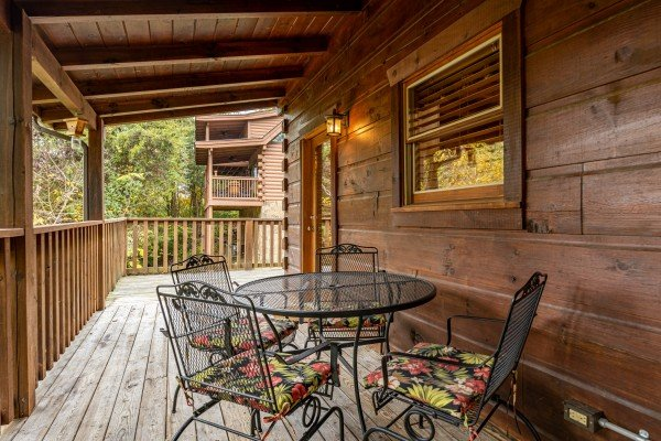 Outdoor dining for four on a covered deck at Livin' Simple, a 2 bedroom cabin rental located in Pigeon Forge