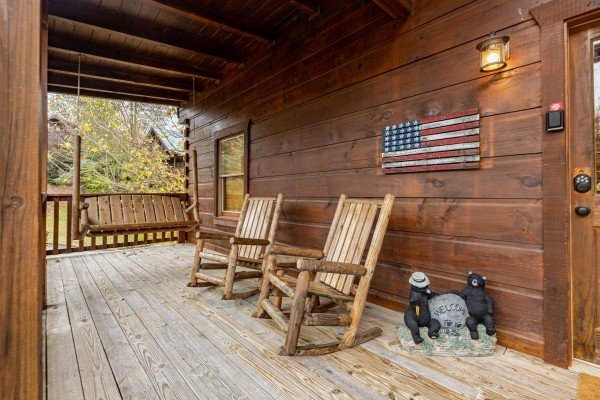 Swing and rocking chairs on a covered porch at Livin' Simple, a 2 bedroom cabin rental located in Pigeon Forge