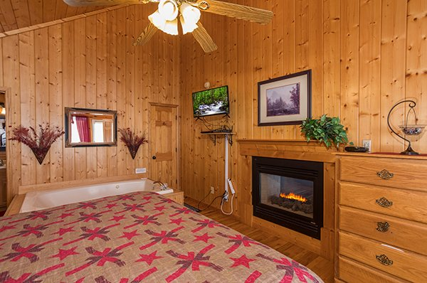 Bedroom with a chest of drawers, fireplace, TV, and jacuzzi at I Do, a 1 bedroom cabin rental located in Pigeon Forge
