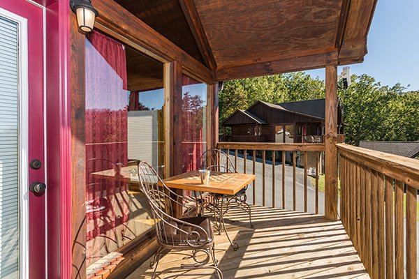 Bistro set on the covered deck at I Do, a 1 bedroom cabin rental located in Pigeon Forge