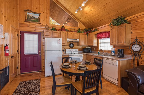 Dining space for four in the kitchen with white appliances at I Do, a 1 bedroom cabin rental located in Pigeon Forge
