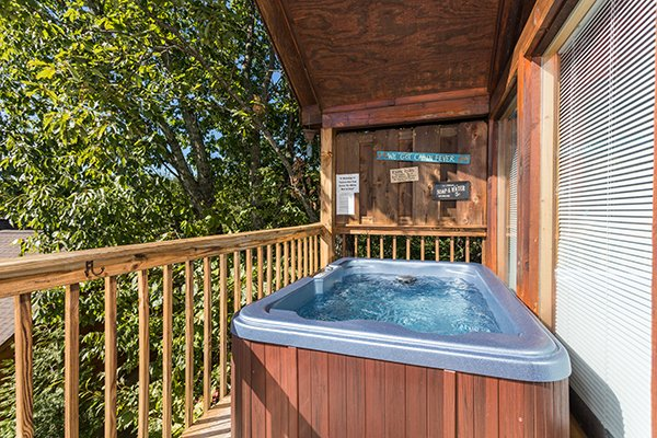 Hot tub on a covered deck at I Do, a 1 bedroom cabin rental located in Pigeon Forge