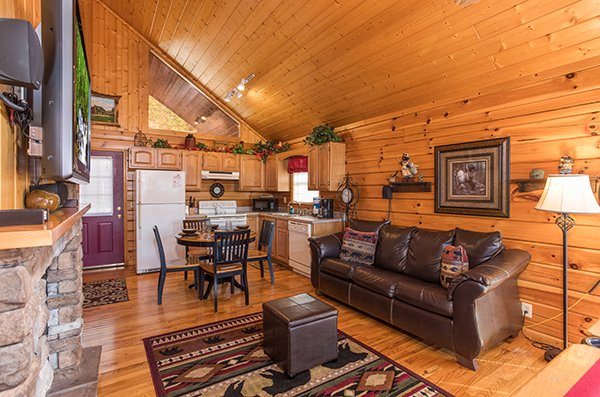 Living room with TV, fireplace, and sofa in the shared open first floor at I Do, a 1 bedroom cabin rental located in Pigeon Forge