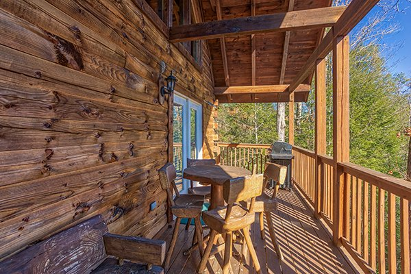 Dining table for four on the covered deck at Mountain Top View, a 3 bedroom cabin rental located in Gatlinburg