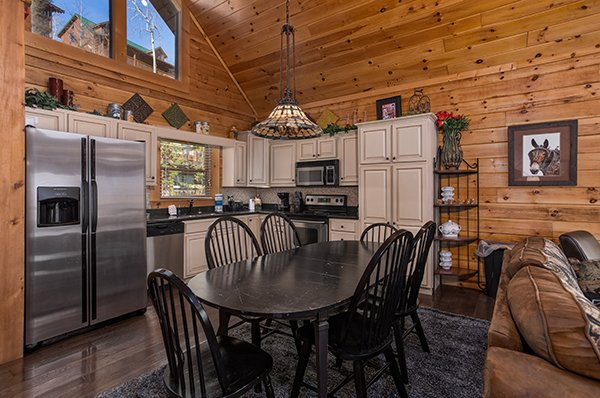 Dining table for six and kitchen with stainless appliances at Mountain Top View, a 3 bedroom cabin rental located in Gatlinburg