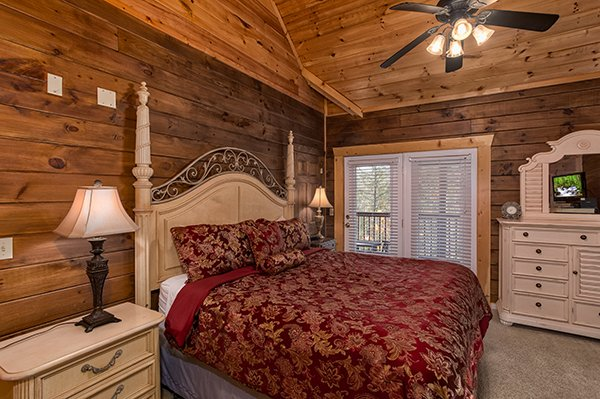 Bedroom with a king bed, dresser with mirror, and a TV at Mountain Top View, a 3 bedroom cabin rental located in Gatlinburg