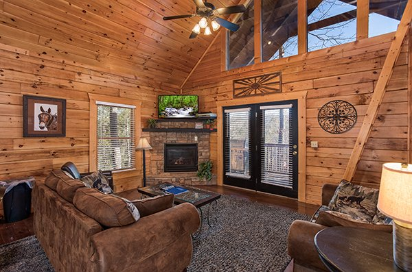 Living room with vaulted ceiling, deck access, fireplace, and TV at Mountain Top View, a 3 bedroom cabin rental located in Gatlinburg