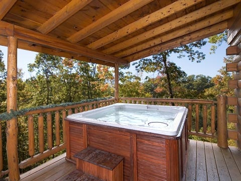 hot tub under a covered deck at gettin' lucky a 1 bedroom cabin rental located in gatlinburg