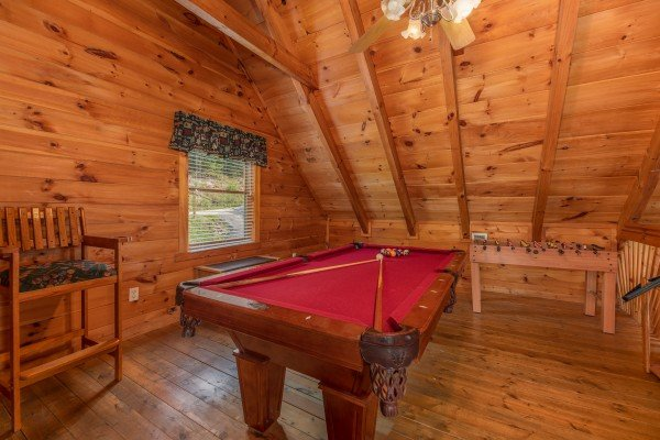 Pool table and foosball table in the game room at American Beauty, a 2 bedroom cabin rental located in Pigeon Forge