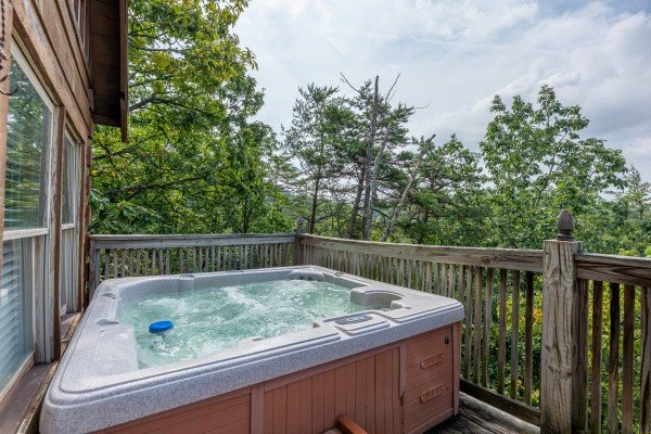 Hot tub on the porch at American Beauty, a 2 bedroom cabin rental located in Pigeon Forge