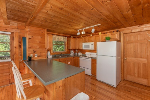 Kitchen with white appliances at American Beauty, a 2 bedroom cabin rental located in Pigeon Forge