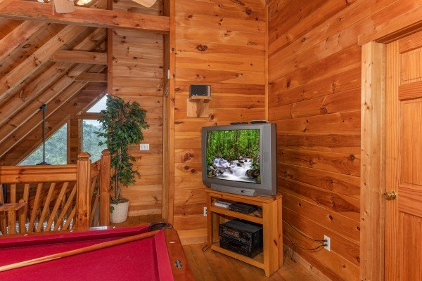TV in the game room at American Beauty, a 2 bedroom cabin rental located in Pigeon Forge
