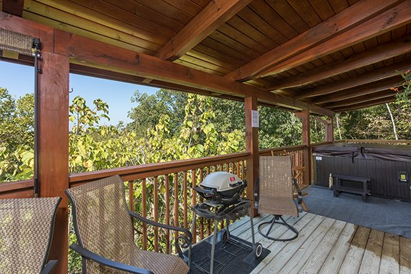 Grill and hot tub on the covered deck at Lake Life, a 4 bedroom cabin rental located in Sevierville