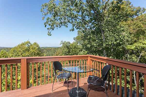 Bistro set on the deck surrounded by trees at Lake Life, a 4 bedroom cabin rental located in Sevierville
