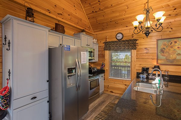 Kitchen with granite counters, stainless appliances, and white cabinets at Lake Life, a 4 bedroom cabin rental located in Sevierville